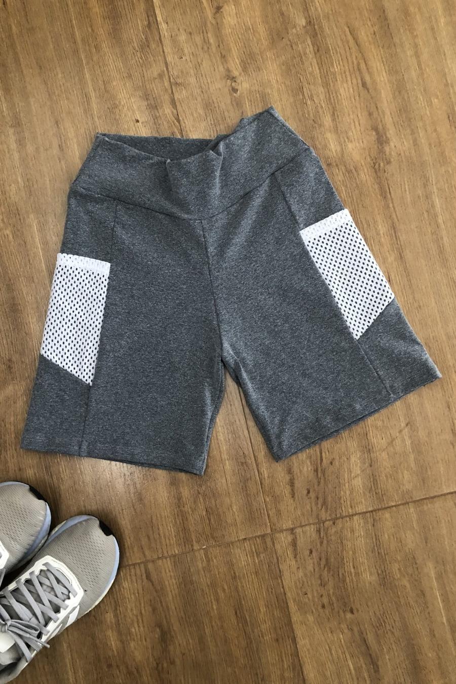 Short fitness cinza em tecido suplex com bolso e recorte branco na lateral